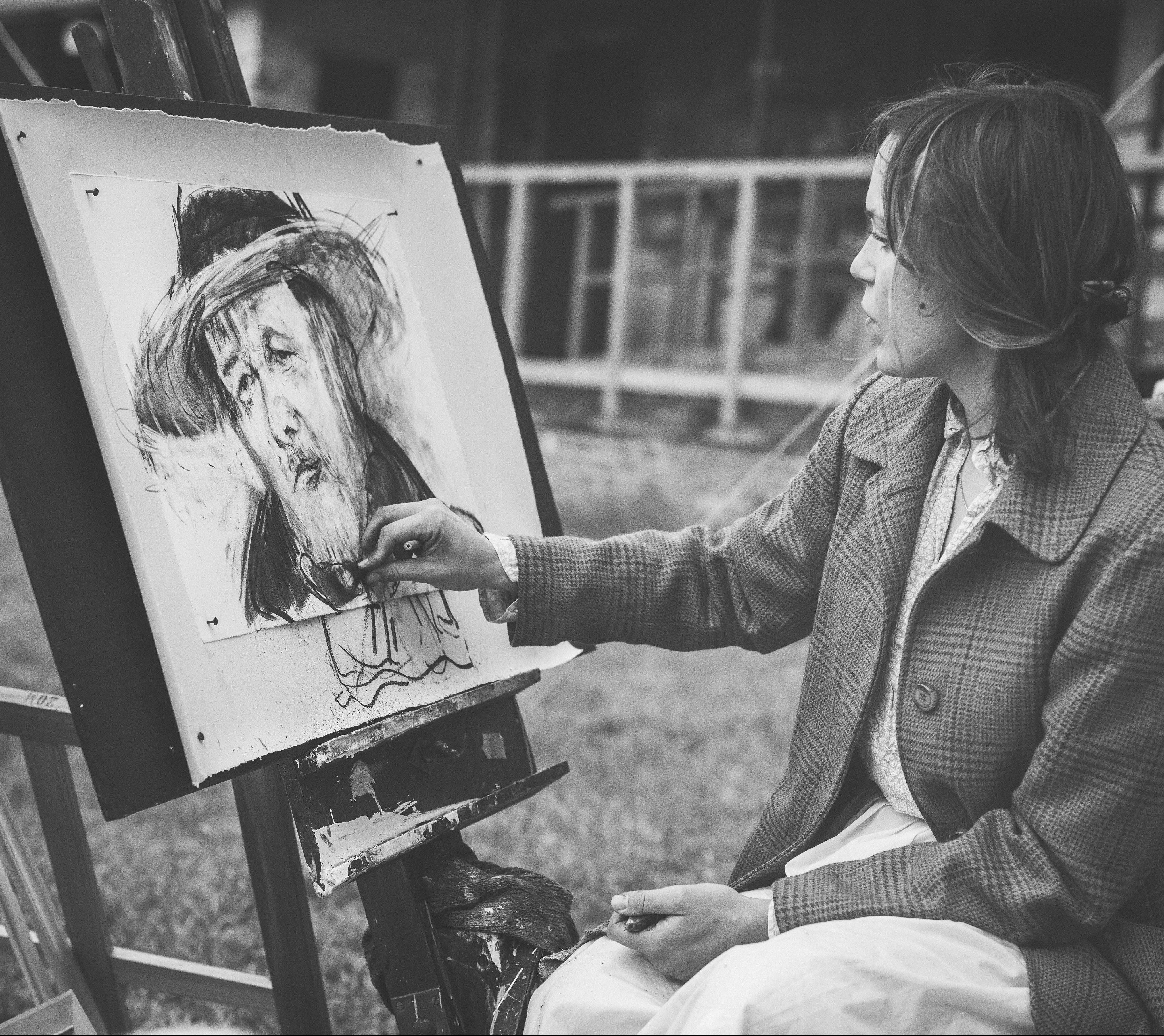 Imagen de una mujer pintando un cuadro en blanco y negro, mujeres artistas
